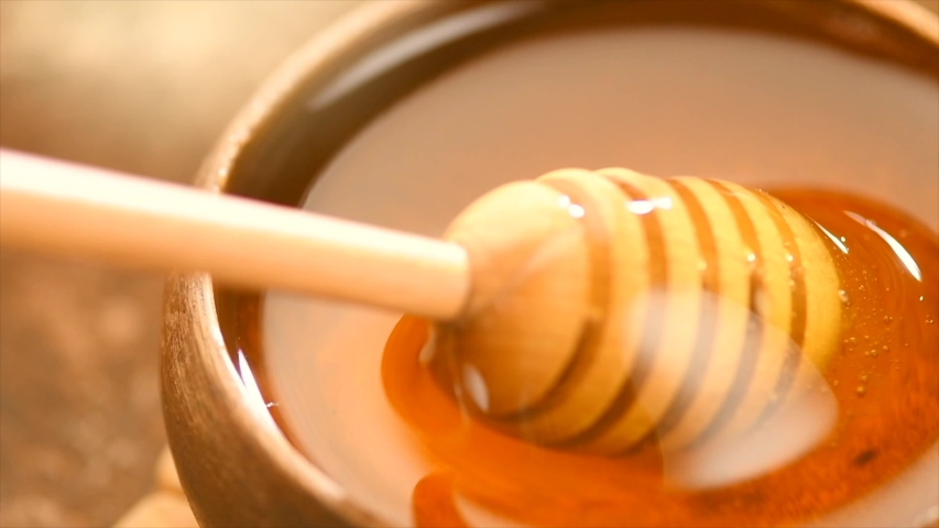 Honey dripping, pouring from honey dipper in wooden bowl.  Close-up. Healthy organic Thick honey dipping from the wooden honey spoon, closeup. 4K UHD video footage. Slow motion Royalty-Free Stock Footage #1054769384