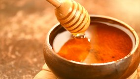 Honey dripping, pouring from honey dipper in wooden bowl.  Close-up. Healthy organic Thick honey dipping from the wooden honey spoon, closeup. 4K UHD video footage. Slow motion.