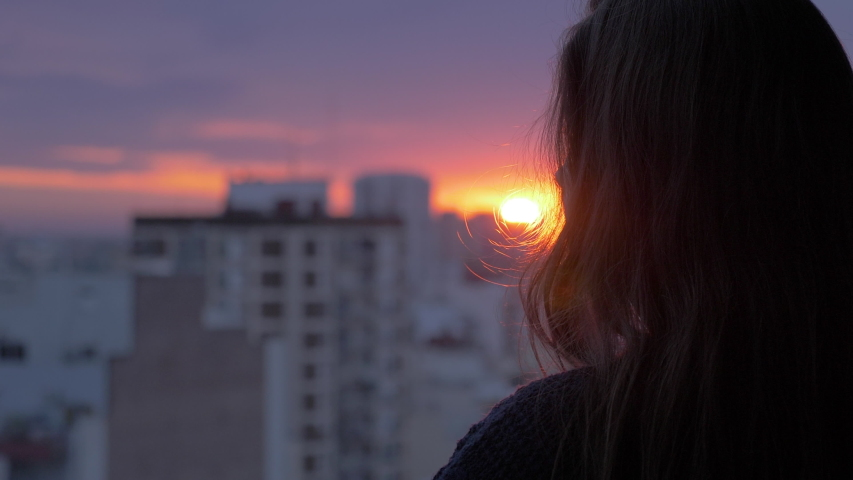 Woman looks out at urban city in the distance as day turns to night Golden Hour Sunset View With Clouds 4K Slow Motion | Shutterstock HD Video #1054769987
