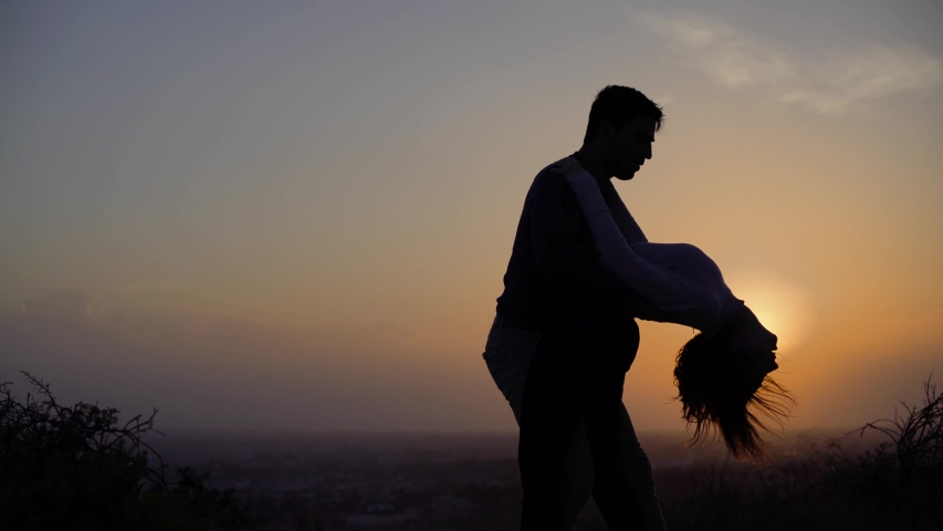 Young dancers couple dancing passionate Latin American dance bachata outdoors in nature at sunset