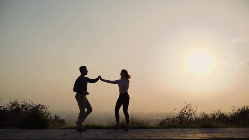 Defocused silhouettes of dancers practising salsa moves and dancing at sunset against skyline in background