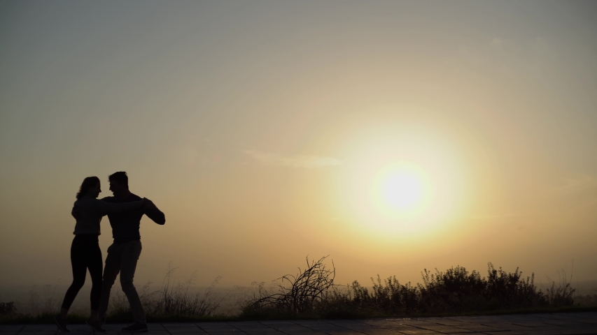 Silhouettes of girlfriend and boyfriend dancers practising hobby and dancing salsa in street at sunset
