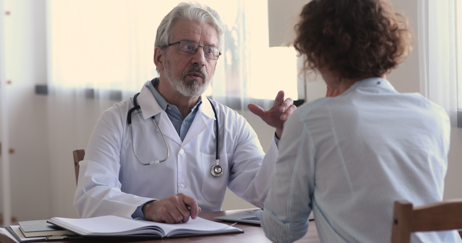 Serious focused middle aged hoary physician in medical coat sitting at table, consulting female patient about illness or surgery. Rear view young woman listening to old doctor at checkup meeting.