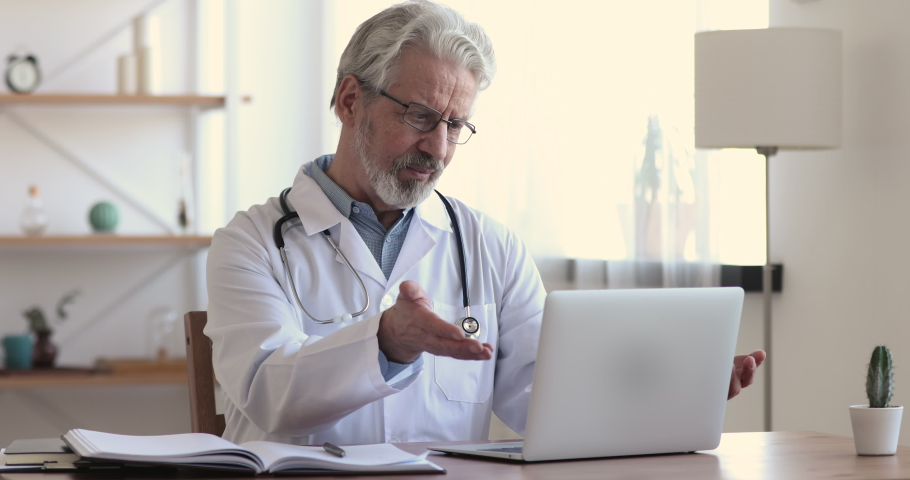 Happy older hoary male doctor in white uniform and glasses looking at computer screen, waving hello to distant client, giving professional consultation online to patient remotely from clinic office. Royalty-Free Stock Footage #1054771364