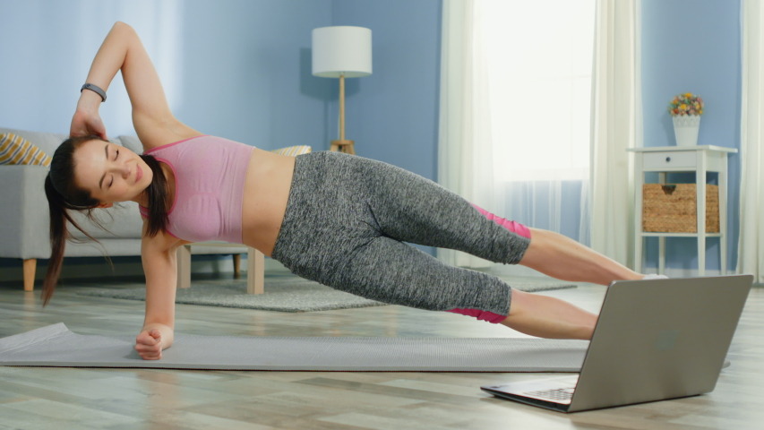 Young strong woman is training at home, standing in side plank, building strong core, focused and motivated, workout with online trainer using laptop, slow motion. | Shutterstock HD Video #1054772066