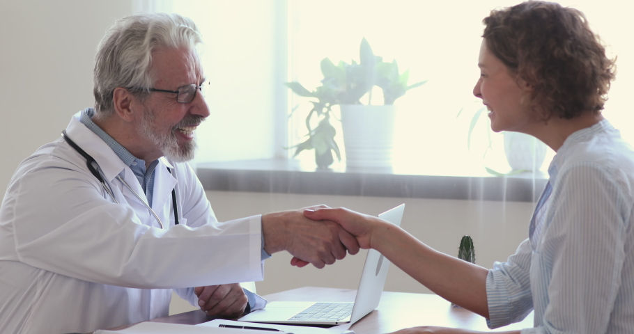 Side view smiling young female patient shaking hands with happy middle aged mature male doctor in white uniform, thanking for help or feeling excited about healthcare treatment results at meeting. Royalty-Free Stock Footage #1054784201