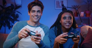 Happy young people playing video games on console while sitting on couch in front of tv. Millennial couple spending fun time together at home.Room with warm and neon lights.