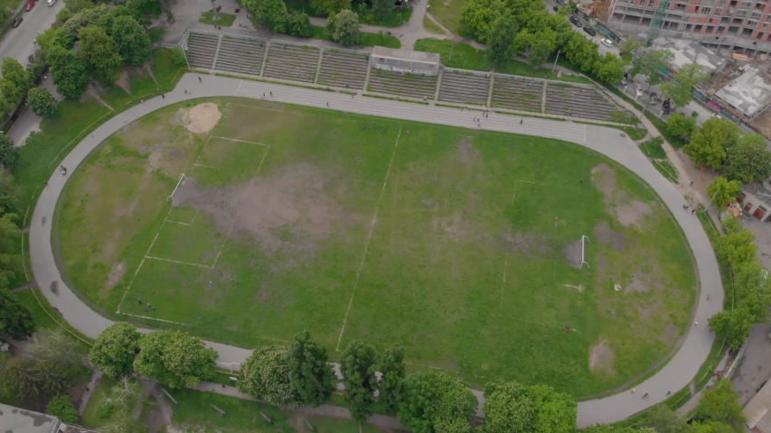 Old stadium aerial poor area sport people are running camera movement | Shutterstock HD Video #1054788137