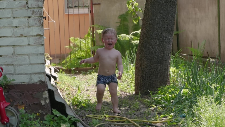 Naked boy is crying hysterics wet toddler 2 years old in backyard slow motion | Shutterstock HD Video #1054788158