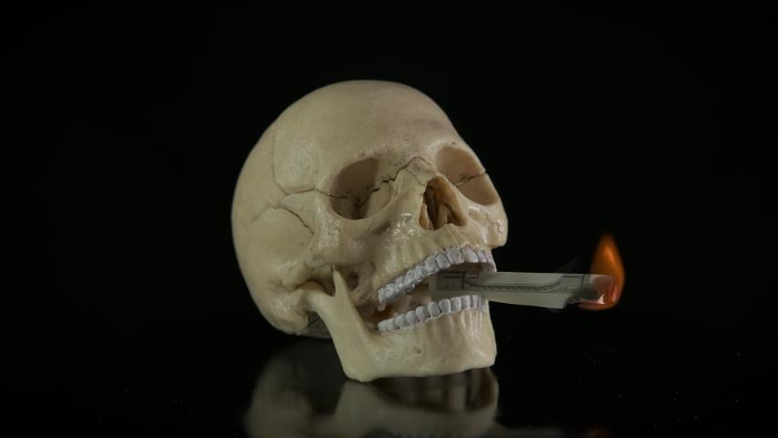 Pull money for nothing. A view of burning money in the human skull mouth. | Shutterstock HD Video #1054788524
