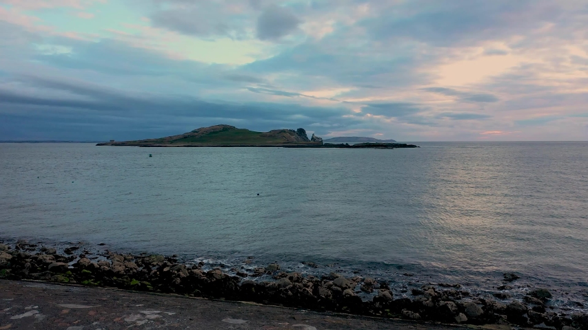 Aerial view of Ireland's Eye island viewed from the Howth harbor at  sunrise on a cloudy day.small uninhabited island off the coast of County Dublin | Shutterstock HD Video #1054789709