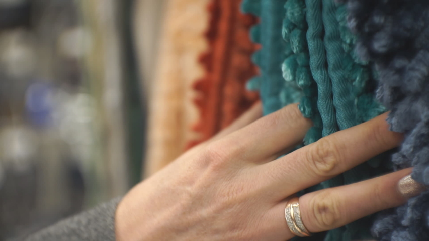 A woman runs her hand over soft multi-colored carpets, checking their quality. Tactile sensations.   Shutterstock HD Video #1054803641