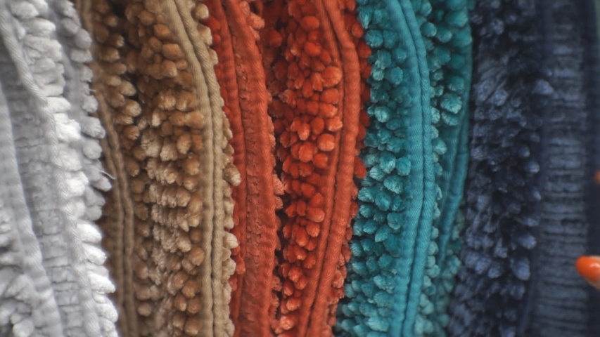 A woman runs her hand over soft multi-colored carpets, checking their quality. Tactile sensations.   Shutterstock HD Video #1054803644