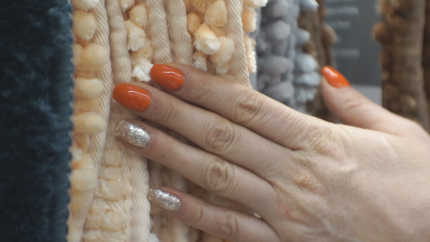A woman runs her hand over soft multi-colored carpets, checking their quality. Tactile sensations.   Shutterstock HD Video #1054803656