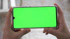 Close up Horizontal hands holding smartphone with green screen. Green screen mobile phone with chroma key. Perfect for product placement.