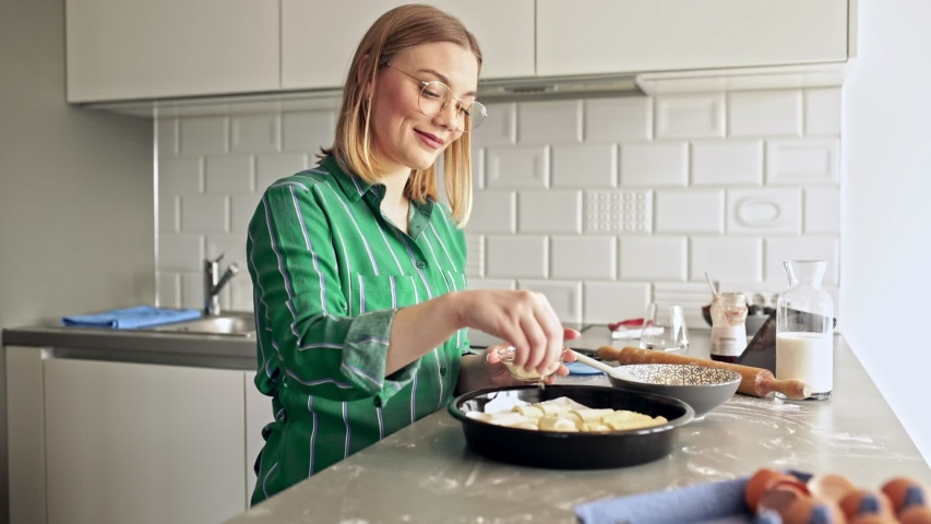 Portrait of young smiling woman making croissants in kitchen at home, sprinkle them with sesame seeds. | Shutterstock HD Video #1054807226