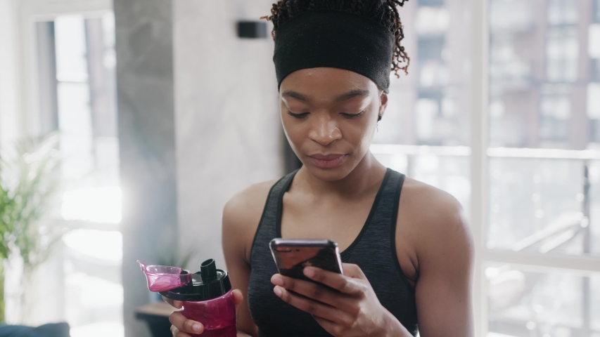 Portrait of charming african american woman in sport clothes lying on exercise mat after sports training, browsing social media content online on cellphone in domestic room, expressing positivity. Royalty-Free Stock Footage #1054807346