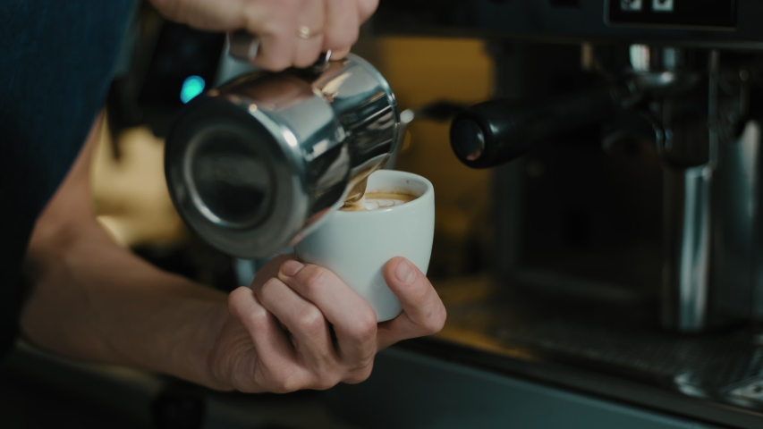 Barista making latte art in  specialty coffee shop. Professional man making pouring stream milk with espresso  | Shutterstock HD Video #1054807808