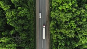 One Semi Truck with white trailer and cab driving / traveling alone on dense flat forest asphalt straight empty road, highway top down view follow vehicle aerial footage / Freeway trucks traffic