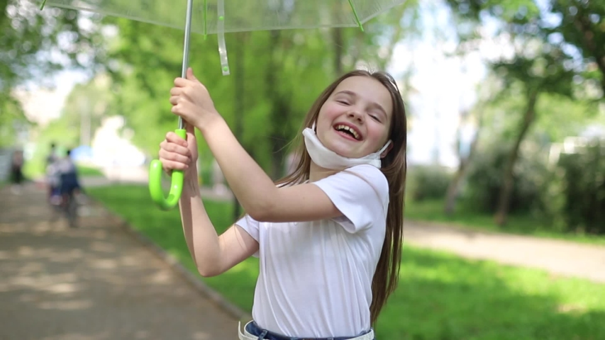 Happy child rejoices over end of coronavirus pandemic (COVID-19), and breathes fresh air in city park   Shutterstock HD Video #1054809800