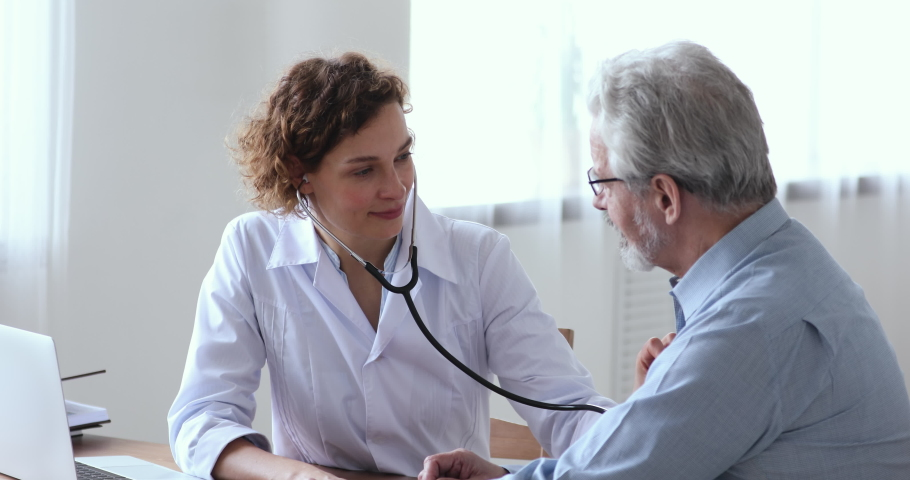 Focused young female cardiologist listening heartbeat of old senior male patient at checkup meeting in clinic office. Skilled 30s woman doctor checking lungs of mature middle aged man in hospital. Royalty-Free Stock Footage #1054810277