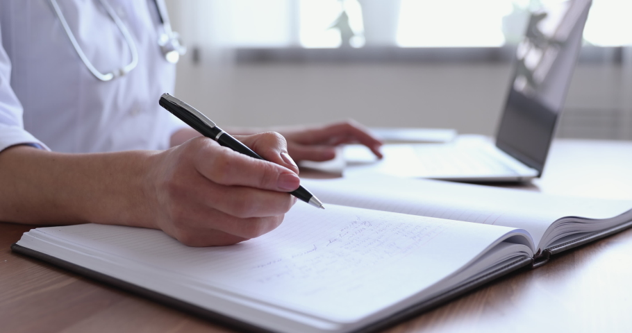 Close up young female doctor writing notes in registration album, managing patients appointments at workplace. 30s general practitioner handwriting receipt, consulting clients online by computer app. Royalty-Free Stock Footage #1054813130