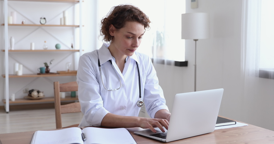 Focused 30s female general practitioner in white uniform sitting at workplace, doing paperwork and using medical software application on computer, involved in research or making report at clinic.