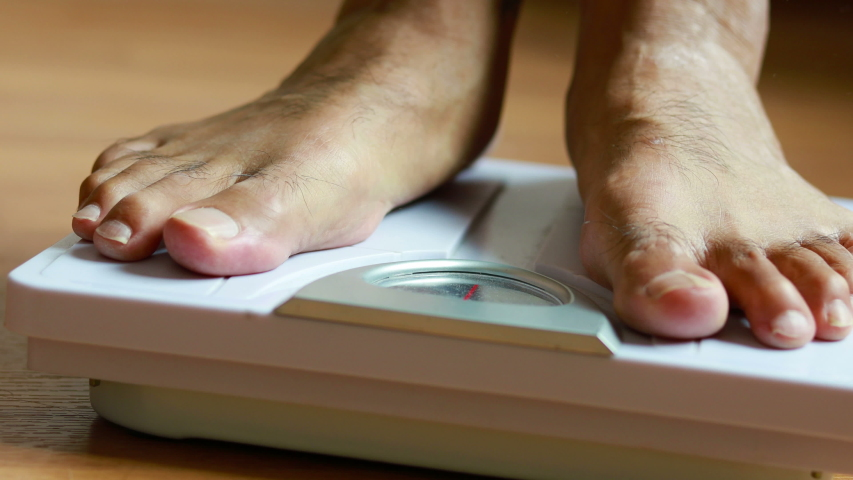 Close up man's feet body weight scales for measure weight loss.Weighing scale to healthy slimming concept.