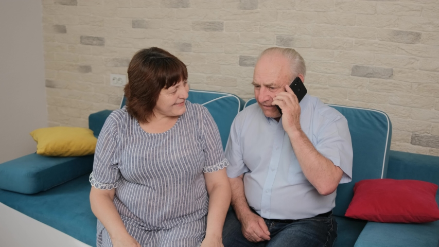 Caucasian senior couple was told a good news. Man is talking at phone with his son that told him the great news, happy couple embrace each other and smile