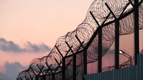 A telephoto video clip of a prison fence at dusk with a piece of plastic bag moving with the wind and so do the clouds in the background.