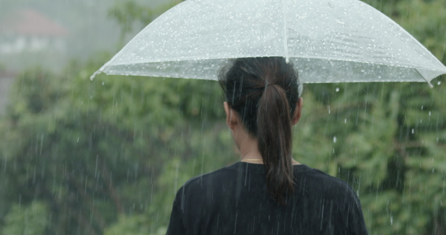 Woman is holding umbrella walking alone under the rain on the road in the rainy day. Slow motion shot. Royalty-Free Stock Footage #1054818209