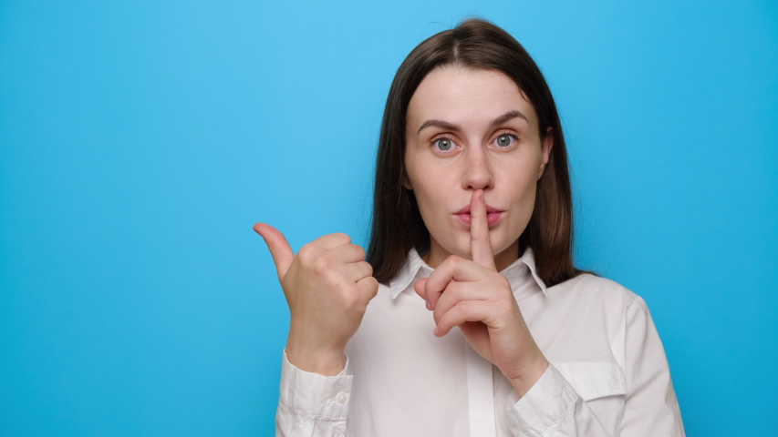 Young caucasian woman point with finger at blank copy space aside, brunette girl make hush be quiet gesture, tell about show secret sale offer, dressed in white shirt, isolated on blue background | Shutterstock HD Video #1054818446