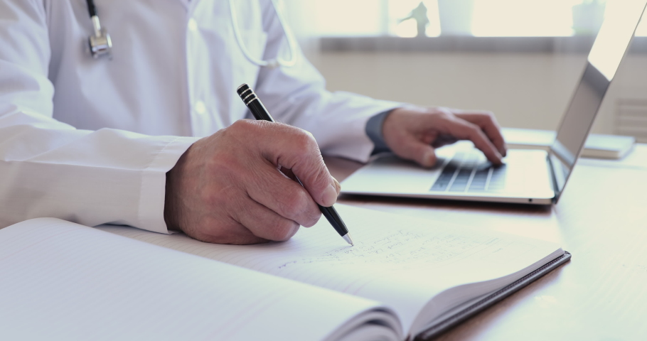 Close up wrinkled male hands writing information in medical registration journal. Old mature doctor therapist working at office, using healthcare software application on computer, handwriting notes.