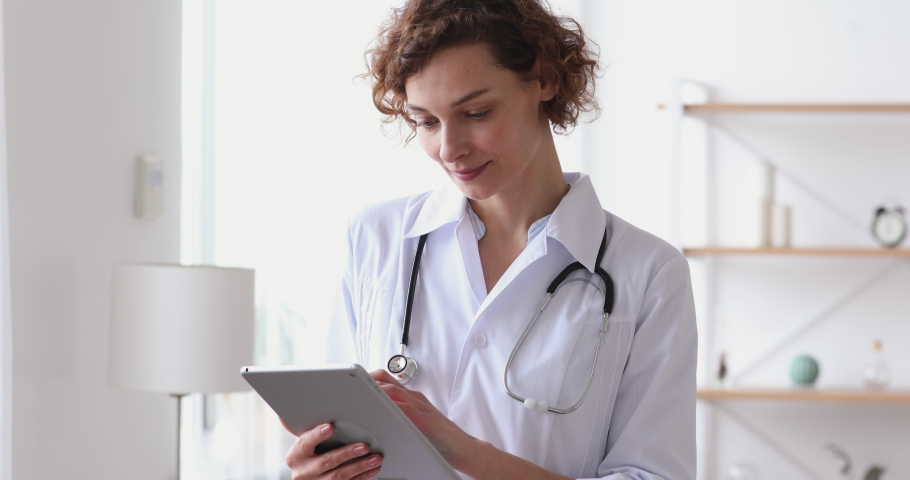 Smiling young female therapist using online healthcare app on digital computer tablet, planning patients appointment in clinic office. Happy doctor general practitioner holding touchpad in hands.