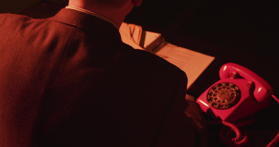 Unidentified man behind desk on corded rotary phone. Man picks up and dials rotary phone then hangs up. Stylistic spy movie or film noir. (Shot on RED) 4K