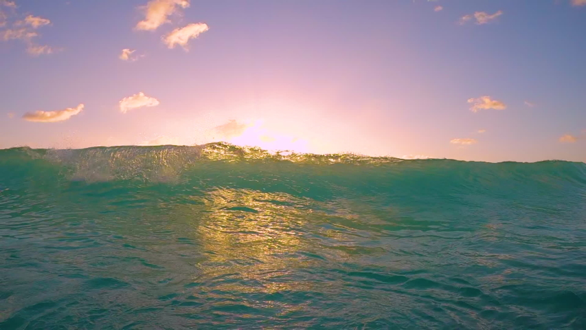 SLOW MOTION, UNDERWATER: Massive turquoise barrel wave breaks over the camera on a sunny summer evening in the scenic Caribbean. Cinematic view of a crystal clear breaking ocean wave at golden sunset.