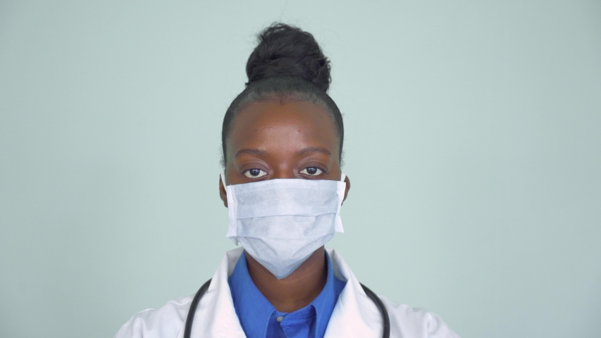 African american female doctor wear white medical coat stethoscope face mask look at camera closeup headshot portrait. Brave proud black hero physician on grey, healthcare safety, medicine protection Royalty-Free Stock Footage #1054823147