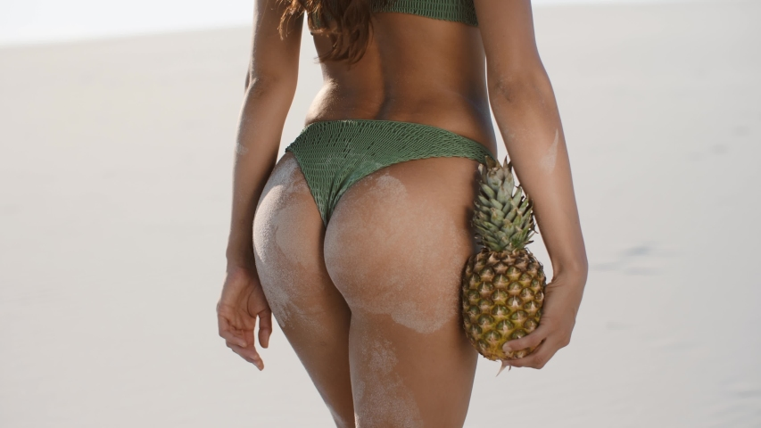 Female tanned buttocks in sand, sexy back. Sporty back of a beautiful woman in green bikini with a pineapple in her hands on the beach tropical background with copyspace.
