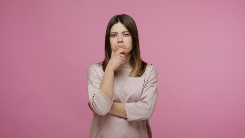 Pensive brunette woman rubbing chin while solving serious problem in mind, nodding approvingly, thinking over smart idea, pondering and musing answer. indoor studio shot isolated on pink background Royalty-Free Stock Footage #1054825190