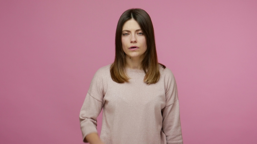 You tell lie! Brunette young woman touching nose and frowning displeased, angry about deception, showing liar gesture, suspecting cheats, falsehood. indoor studio shot isolated on pink background | Shutterstock HD Video #1054825208