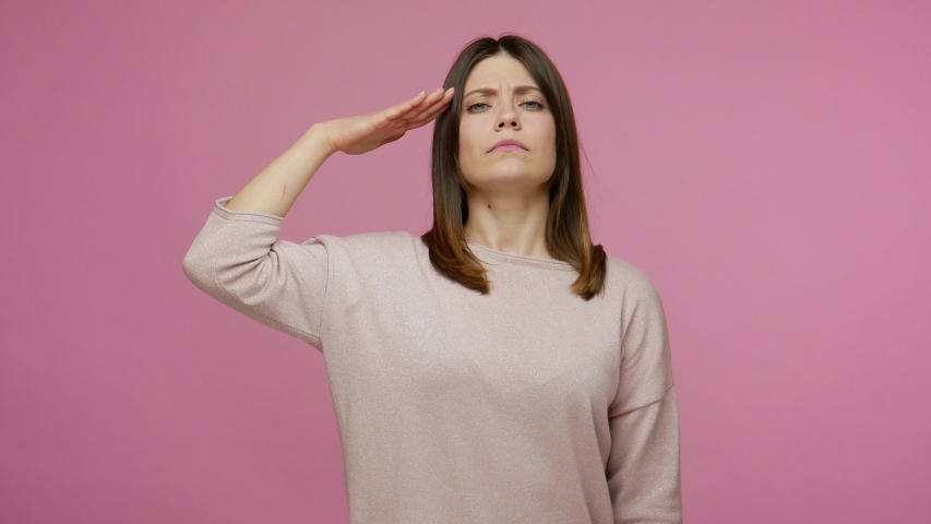 Yes sir! Very responsible brunette young woman saluting and nodding approvingly, listening attentive to order with patriotic face, discipline concept. indoor studio shot isolated on pink background | Shutterstock HD Video #1054825244