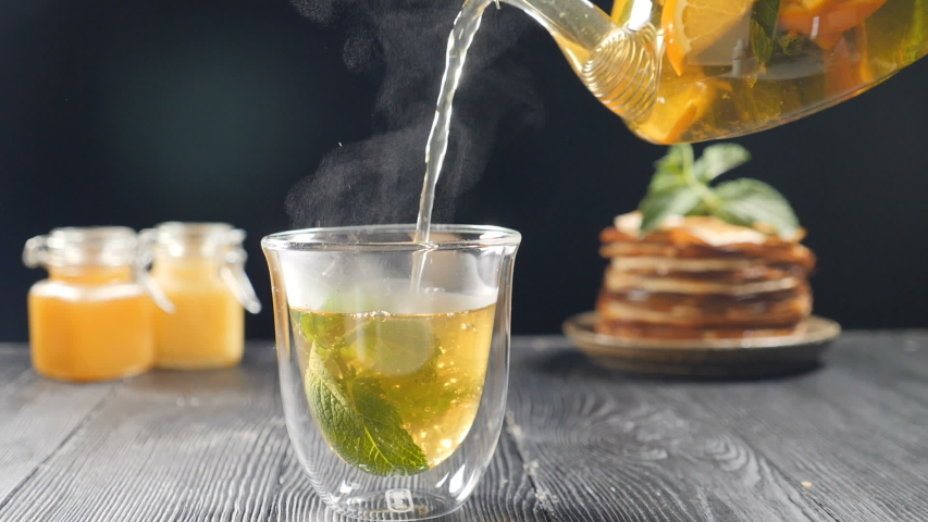 Pouring tea with orange, lemon and lime out of transparent tea pot into glass with nint.Brewing tea with honey and pancakes in background. Slow motion tea. Full hd Royalty-Free Stock Footage #1054826168
