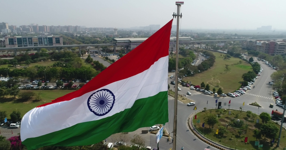 Drone shot of the Indian Tricolor Flag Fluttering in a commercial complex in Gurugram (old name: Gurgaon), India- Mid Shot Royalty-Free Stock Footage #1054828961