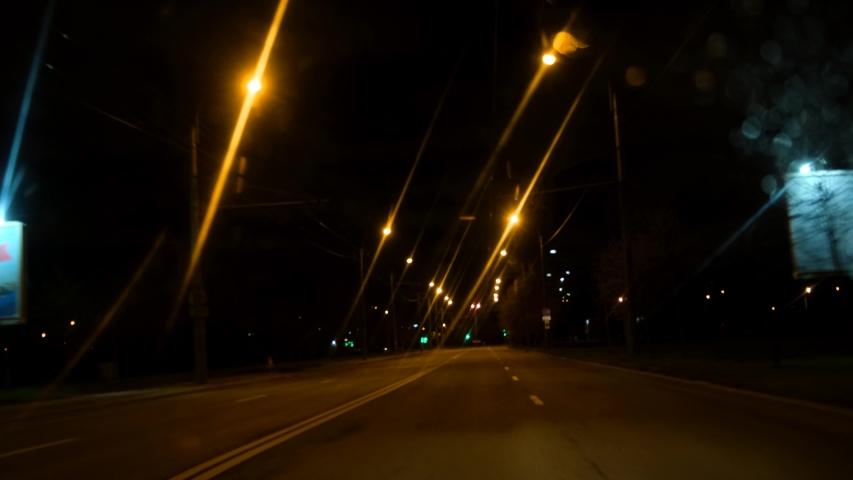 4k. night drive on empty city street road from the window of speed car, street light blurring after rain.
