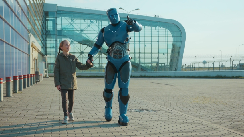 Happy child girl walking with humanoid robot cyborg talking smiling on street outdoors futuristic future machine artificial virtual intelligence innovative communication high-tech slow motion Royalty-Free Stock Footage #1054830734