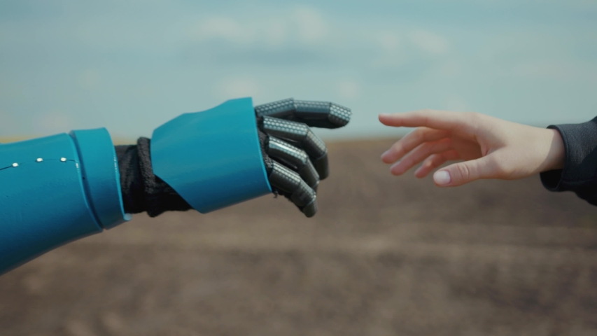 Robot and human pulling hands to reach out each other. Almost reaching robotic cyborg and woman hands outdoors at agricultural field. Human interaction with AI. Future concept. Royalty-Free Stock Footage #1054830737