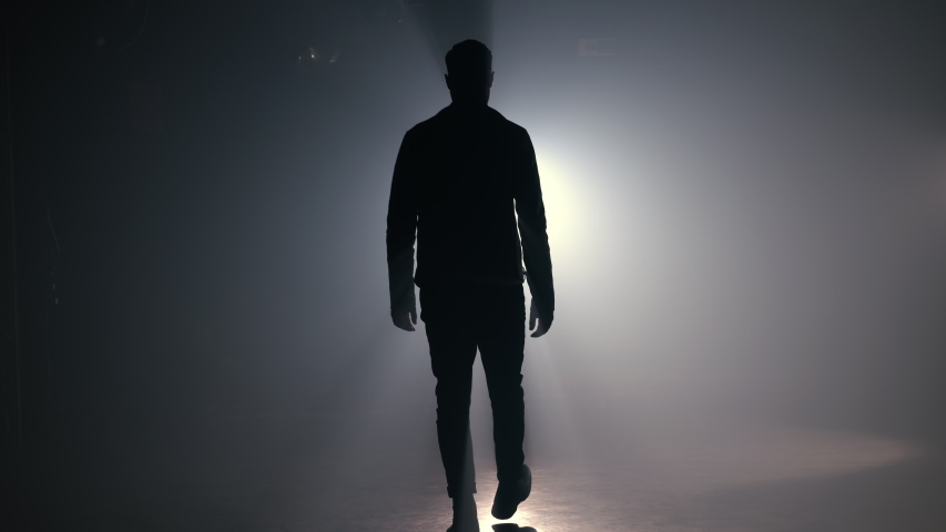 Silhouette of man is walking through smoky studio or scene right from camera | Shutterstock HD Video #1054832207