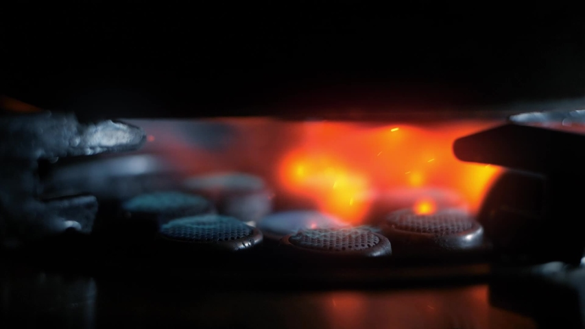 Gas stove being turned on in the dark background, Close up of gas is switching on, appearing blue flame.