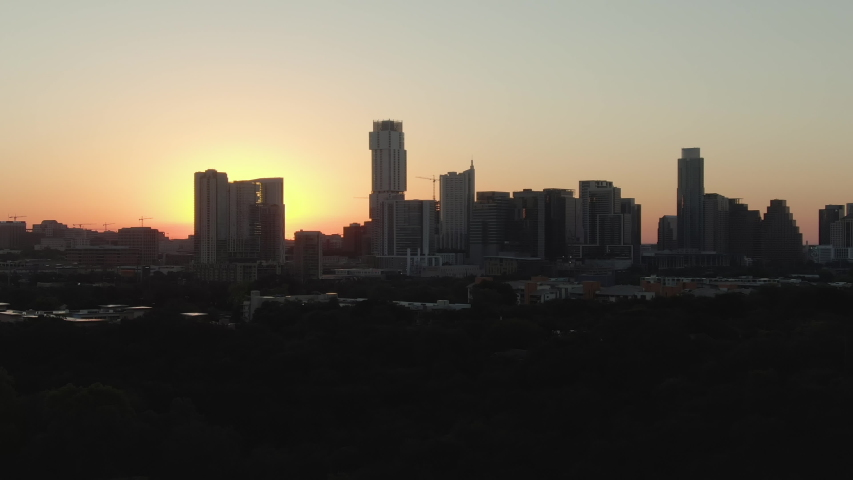 Aerial telephoto tracking shot of downtown Austin, Texas skyline at dawn on a summer day.
