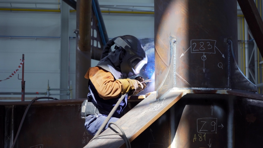 Professional heavy industry worker welder in protective mask and suit works with metal construction on factory. Steel and iron welding construction site. Welding machine with sparks and flashes. | Shutterstock HD Video #1054852787